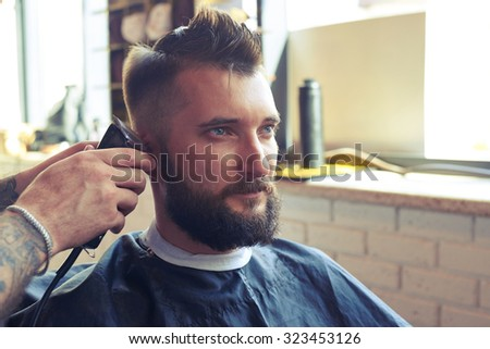 portrait of handsome man with beard in barbershop. barber working with electric razor - stock photo