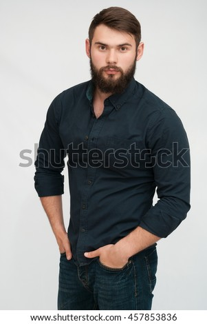 Portrait of handsome man with beard. Serious man in shirt with hands in pockets