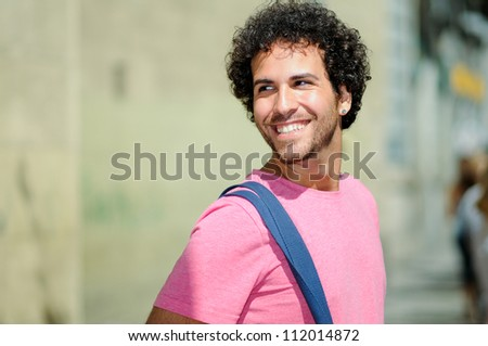 Portrait of handsome man with curly hairstyle, walking in the street - stock photo