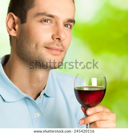 Portrait of handsome man with glass of redwine, outdoor - stock photo