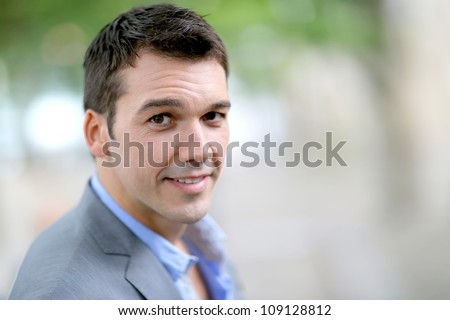 Portrait of handsome man with jacket standing in the street - stock photo