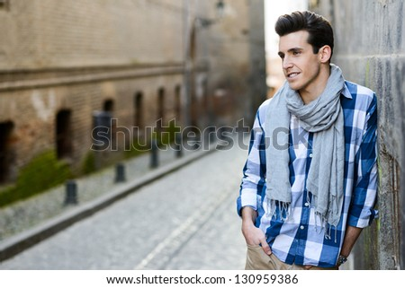 Portrait of handsome man with modern hairstyle smiling in urban background - stock photo