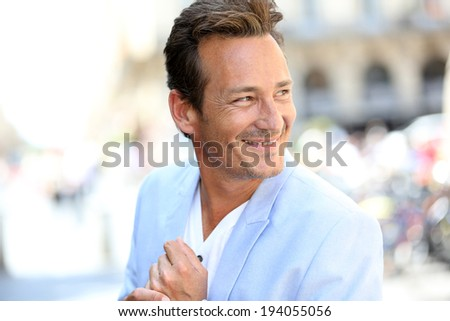 Portrait of handsome mature man in town - stock photo