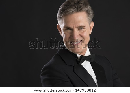Portrait of handsome mature man in tuxedo smiling against black background - stock photo