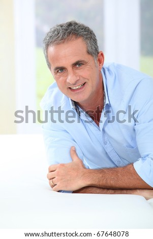 Portrait of handsome mature man laying on sofa - stock photo