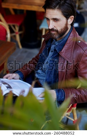 Portrait of handsome mature man with beard holding magazine in the hands looking away, attractive man having a coffee while he reads newspaper - stock photo