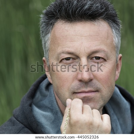 Portrait of handsome mid-adult man posing on summer meadow with blade of grass and looking at camera, image toned. - stock photo
