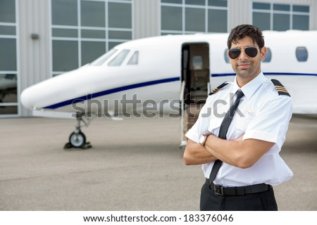 Portrait of handsome pilot with arms crossed standing in front of private jet - stock photo