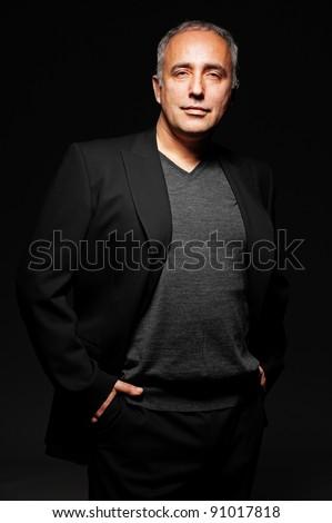 portrait of handsome senior businessman over dark background - stock photo