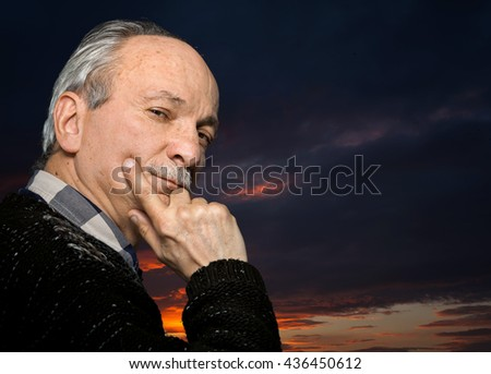 Portrait of handsome senior man with a tired expression against sunset sky