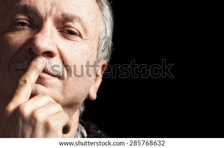 Portrait of handsome senior man with a tired expression isolated on black with copy-space - stock photo