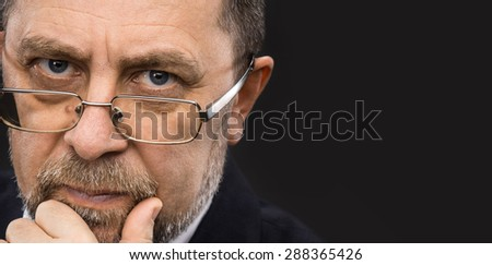 Portrait of handsome senior man with glasses prop up the head with his hand and copy-space - stock photo