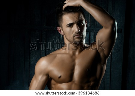 Portrait of handsome sexy sensual muscular stylish young man topless with bare torso and beautiful body standing indoor on wooden background, horizontal picture - stock photo