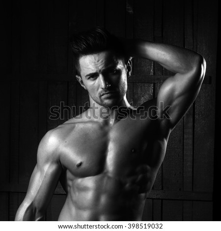 Portrait of handsome sexy sensual muscular stylish young man topless with bare torso and beautiful body standing indoor on wooden background, square picture - stock photo
