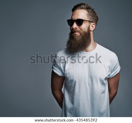 Portrait of handsome single bearded young man with serious expression wearing sunglasses and white short sleeve shirt looking over gray background with copy space - stock photo