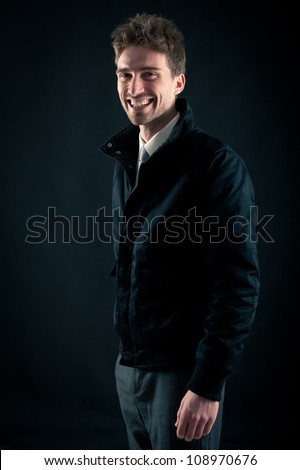 Portrait of handsome, smiling man against dark background. - stock photo