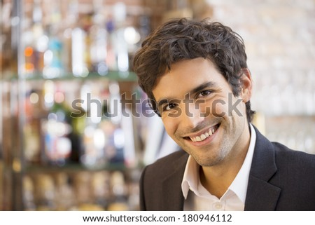 Portrait of handsome smiling man in restaurant, looking camera