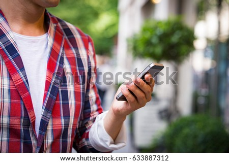 Portrait of handsome smiling stylish man close-up with smart phone in plaid blazer in the summer city. Street style concept. Walking down the sunny city street.