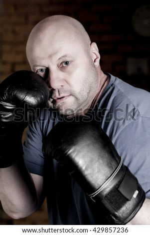 Portrait of handsome sportsman posing with boxing gloves - stock photo