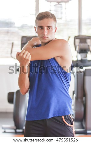 portrait of handsome sporty man stretching his arm at the gym