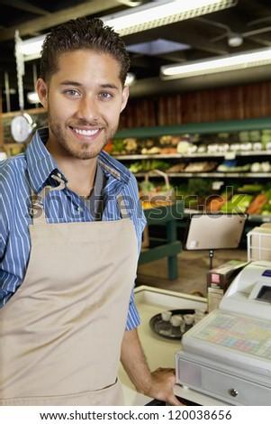 Portrait of handsome store employee standing near cash register in supermarket - stock photo