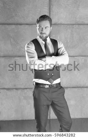 Portrait of handsome stylish bearded young man in elegant blue suit with vest and perfect hair style. Black and white