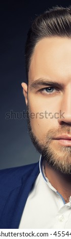 Portrait of handsome stylish caucasian bearded young man in elegant blue suit and white shirt with perfect hair style looking at camera. Toned  - stock photo