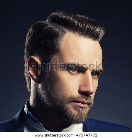 Portrait of handsome stylish caucasian young man in elegant blue suit with perfect hair style. Toned
