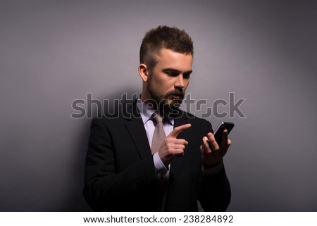 Portrait of handsome stylish man in elegant black suit and beige tie  with phone  looking aside  on grey background  with copy place