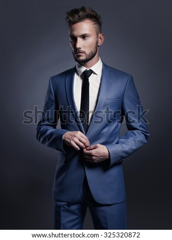 Portrait of handsome stylish man in elegant blue suit - stock photo