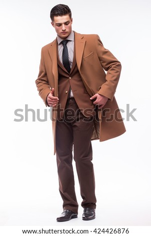 Portrait of handsome stylish man in elegant brown suit and coat on white - stock photo