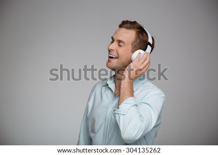 Portrait of handsome stylish young man on grey background. Smiling man listening to music with large white headphones and with his eyes closed