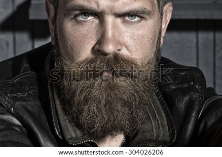 Portrait of handsome sullen unshaven male with long beard and handlebar moustache in black leather jacket sitting looking forward on workshop background, horizontal picture - stock photo