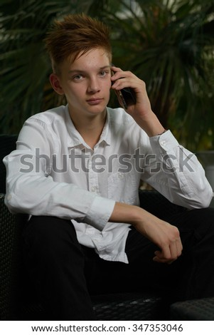 Portrait of handsome teenager boy outdoors using mobile phone - stock photo