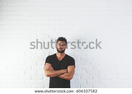 Portrait of handsome, thoughtful young man with folded amrs looking up on white brick background