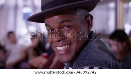 Portrait of Handsome young black hipster man smiling and laughing with group of friends partying in background - stock photo