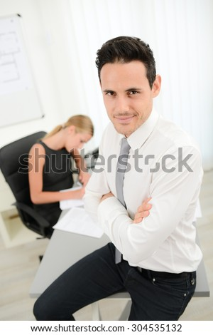 portrait of handsome young business man posing in office with woman coworker in background - stock photo
