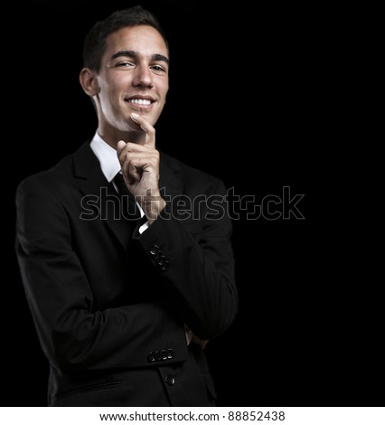 portrait of handsome young business man thinking and looking up against a black background