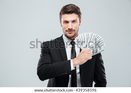 Portrait of handsome young businessman holding money over white background - stock photo
