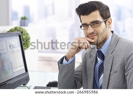 Portrait of handsome young businessman in bright office. - stock photo