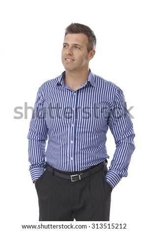 Portrait of handsome young businessman in shirt and trousers standing with hands in pockets. - stock photo