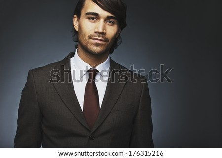 Portrait of handsome young businessman in suit looking at camera. Asian male fashion model in office attire against black background with copyspace. - stock photo