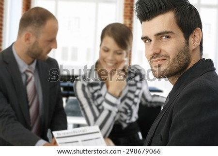 Portrait of handsome young businessman looking at camera, colleagues working at background. - stock photo