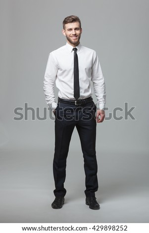Portrait of handsome young businessman standing against gray background. - stock photo