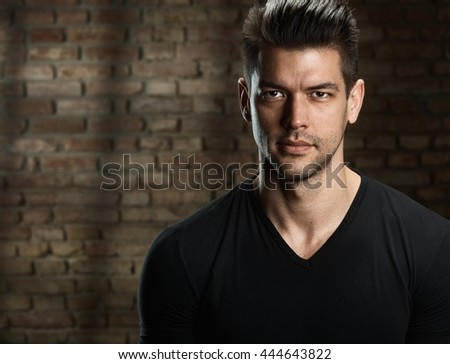 Portrait of handsome young caucasian man, looking at camera. Dark background, copyspace. - stock photo