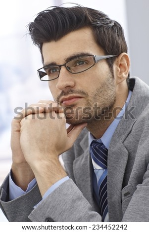 Portrait of handsome young daydreaming businessman looking away. - stock photo