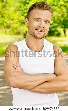 Portrait of handsome young dressed in white man, against green of summer park.