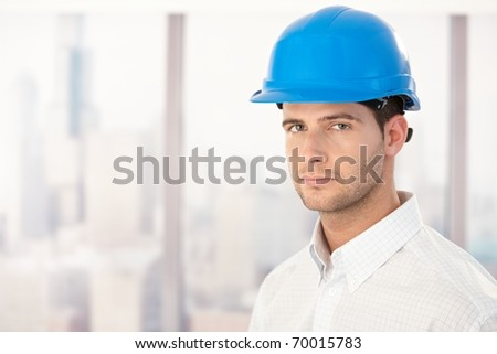 Portrait of handsome young engineer wearing hardhat.? - stock photo