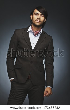 Portrait of handsome young male fashion model posing in dark suit against black background. Stylish man standing with his hands in pocket looking at camera. - stock photo