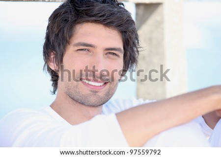 portrait of handsome young man by sea - stock photo